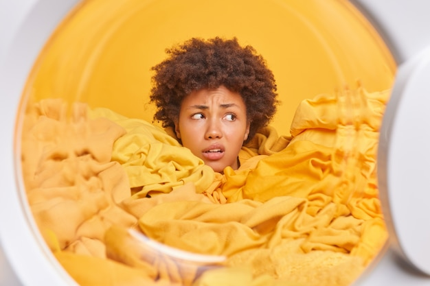 Verbaasde ontevreden krullende afro-amerikaanse huishoudster kijkt weg verdronken in gele vuile was haalt schone kleren uit de wasmachine die de dagelijkse routine en huishoudelijke taken beu is