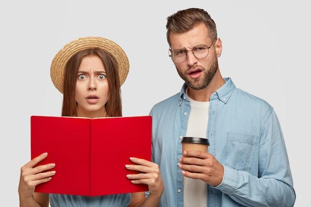 Verbaasde, ontevreden studenten dragen een geopend boek bij zich, lezen informatie