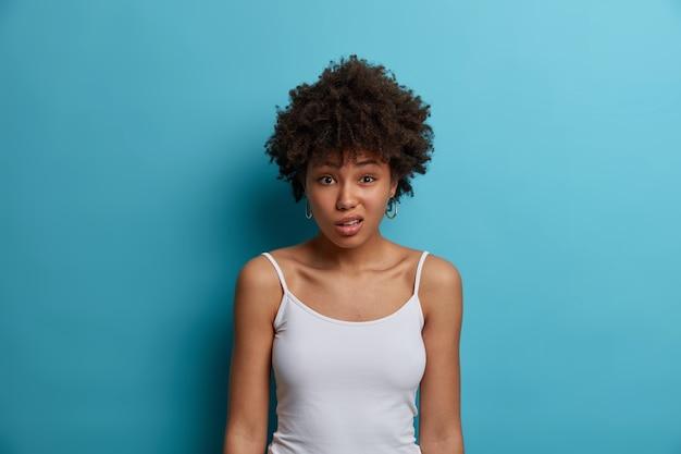 Verbaasde ontevreden vrouw met afro-kapsel, fronst gezicht, reageert op negatief nieuws, hoort onaangename geruchten, draagt casual wit vest, geïsoleerd over blauwe muur. het concept van menselijke gezichtsuitdrukkingen