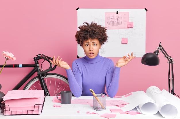 Verbaasde, onwetende jonge vrouw spreidt handpalmen creats architecturaal project maakt onderzoek poses op desktop nonchalant gekleed