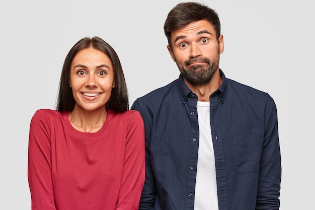 Verbaasde onzekere jonge vrouw en man kijken met twijfelachtige uitdrukkingen naar de camera, proberen een beslissing te nemen