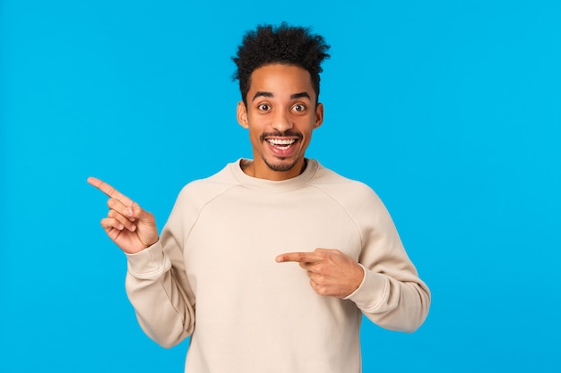 Verbaasde, opgewonden afro-amerikaanse man met afro-kapsel die naar product vraagt, geïnteresseerd in evenement dat naar links wijst en camera opgewonden kijkt, kan niet wachten nieuwjaarsfeest te vieren, blauwe achtergrond