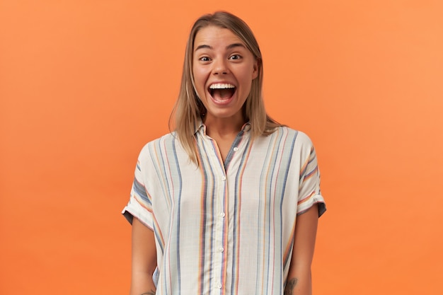 Verbaasde opgewonden jonge vrouw met geopende mond in gestreept shirt kijkt verbaasd en kijkt naar de voorkant geïsoleerd over oranje muur