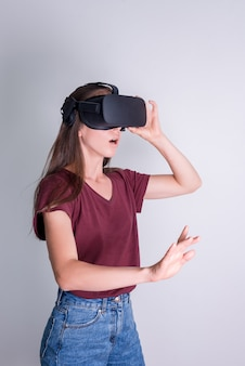Verbaasde positieve vrouw die de hoofdtelefoon van de vr-bril draagt. verbinding, technologie, nieuwe generatie, voortgangsconcept. meisje verrast door iets in virtual reality. studio geschoten op grijs