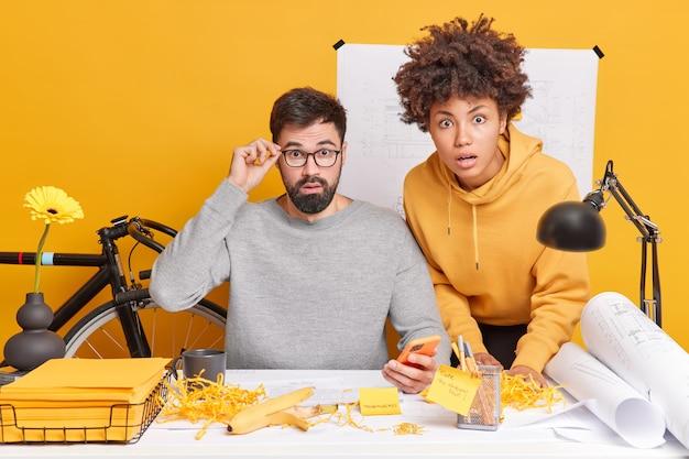 Verbaasde professionele vrouwelijke en mannelijke ingenieurs ontwerpen samen plannen maken blauwdrukken voor toekomstig project verbijsterd om te ontdekken dat grote fout pose op desktop met schetsen eromheen. teamwerk concept