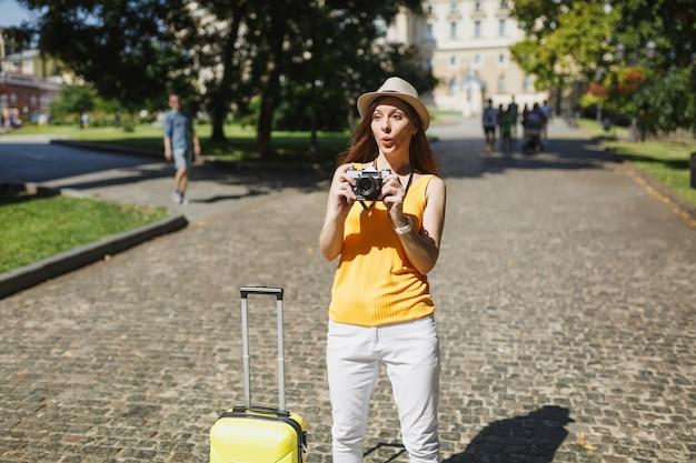 Verbaasde reiziger toeristische vrouw in gele vrijetijdskleding en hoed met koffer die foto's maakt op retro vintage fotocamera buiten. meisje op weekendje weg naar het buitenland. toeristische reis levensstijl.