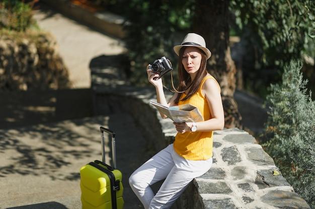 Verbaasde reiziger toeristische vrouw in vrijetijdskleding, hoed met koffer op zoek op stadsplattegrond met retro vintage fotocamera buiten. meisje op weekendje weg naar het buitenland. toeristische reis levensstijl.