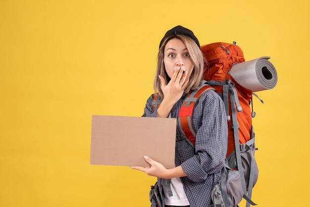 Verbaasde reiziger vrouw met rugzak met karton holding