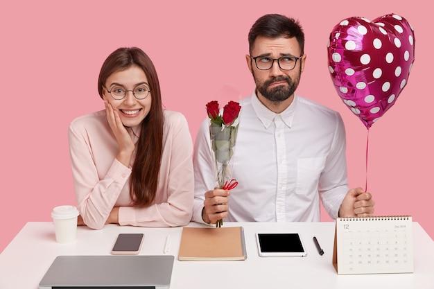 Verbaasde romantische man probeert geschikte woorden te vinden voordat hij verliefd bekent bij vrouwelijke collega, houdt boeket rode rozen en valentijn vast