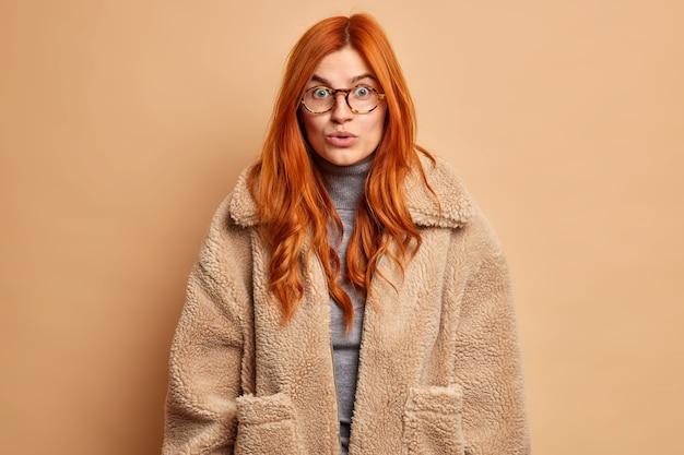 Verbaasde roodharige europese vrouw hoort ongelooflijke geruchten of geheim onder de indruk van iets dat een transparante bril en een bruine vacht draagt.
