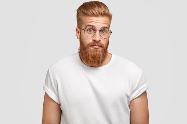 Verbaasde roodharige freelancer voelt zich verrast, kijkt verbijsterd, draagt een ronde bril