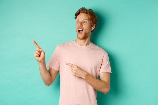 Verbaasde roodharige man in t-shirt die promo bekijkt, hijgend van ontzag en wijzende vingers naar de linkerbovenhoek, staande over muntachtergrond