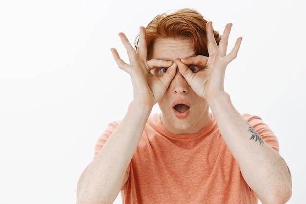 Verbaasde roodharige man kijkt door vingerglazen met onder de indruk gezicht