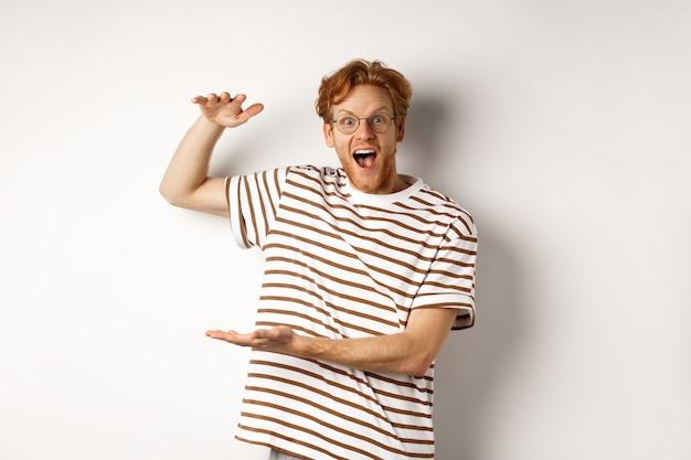 Verbaasde roodharige man met een bril die iets groots toont en naar de camera glimlacht, wauw zegt, staande op een witte achtergrond.