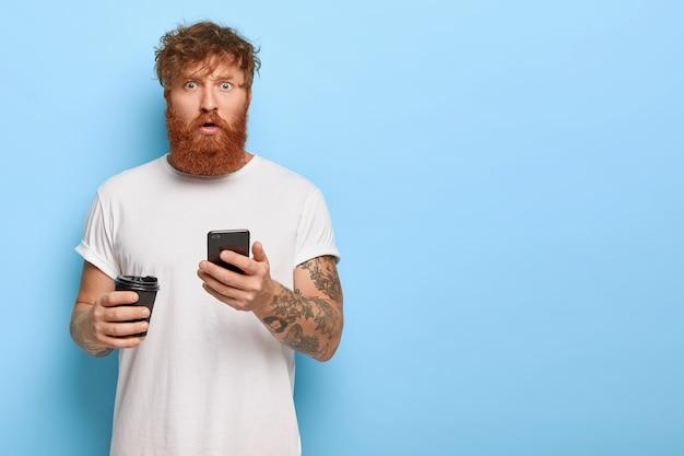Verbaasde roodharige man poseren met zijn telefoon