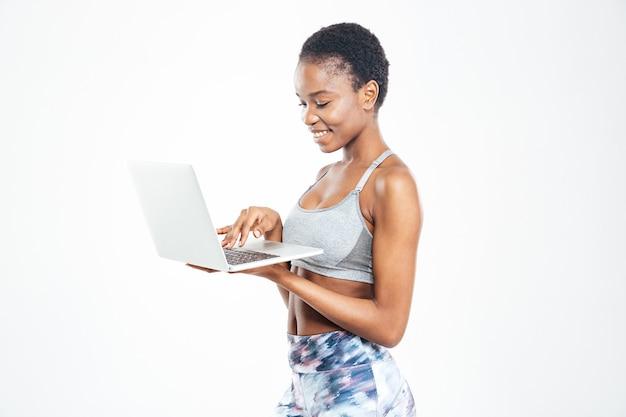 Verbaasde schattige jonge afro-amerikaanse sportvrouw met behulp van een laptop