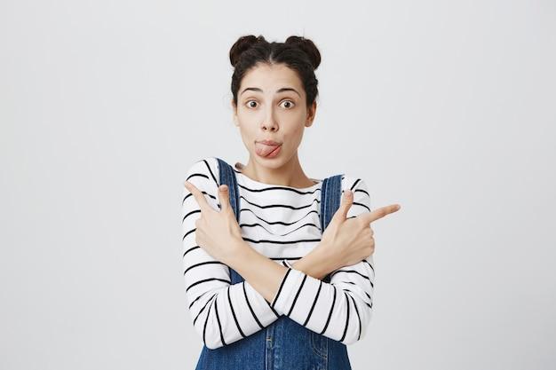 Verbaasde schattige vrouw toont tong, zijwaarts wijzend op promo's