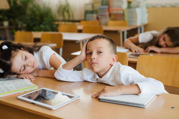 Verbaasde schooljongen aan tafel zitten