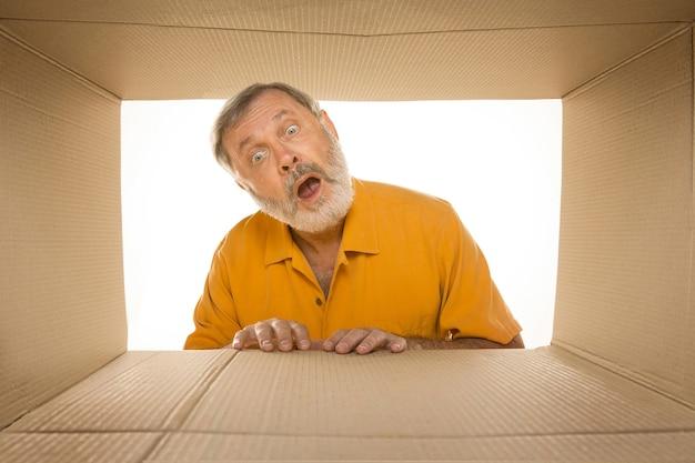 Verbaasde senior man die het grootste postpakket opent dat op wit wordt geïsoleerd. gelukkig mannelijk model bovenop kartonnen doos die naar binnen kijkt.