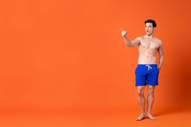 Verbaasde shirtless masculaire kaukasische mens die zijn vinger richt