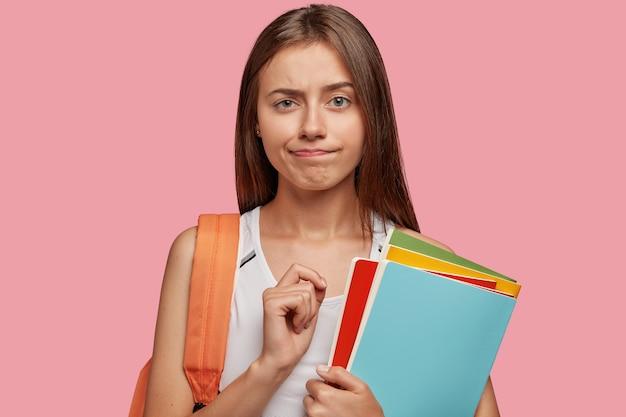 Verbaasde slimme student poseren tegen de roze muur