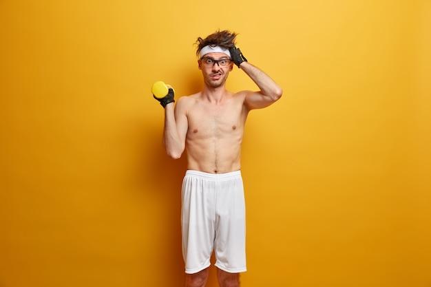 Verbaasde sportman werkt hard om een atletisch lichaam te hebben, oefent 's ochtends met dummbell, valt af, blijft fit en gezond, draagt sporthandschoenen, hoofdband en korte broek. sport en gewichtheffen concept