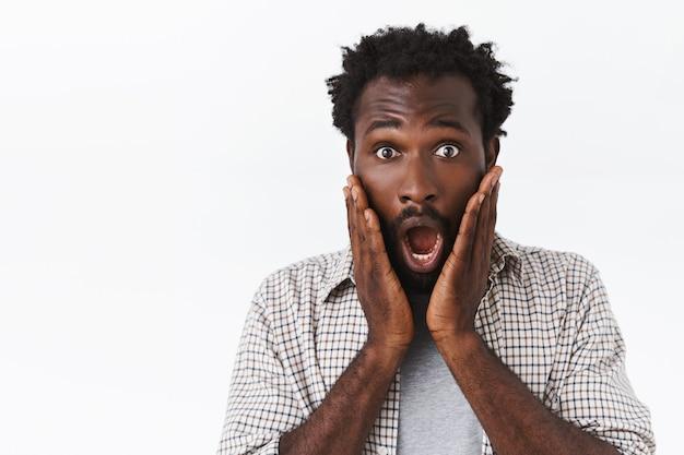 Verbaasde, sprakeloze knappe afro-amerikaanse man, hijgend en schreeuwend van angst of verbazing