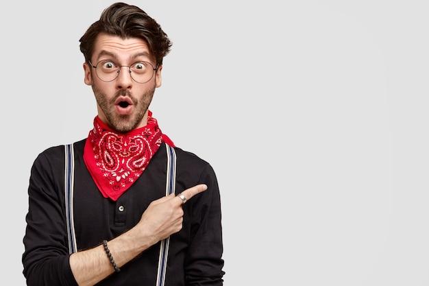 Verbaasde stijlvolle hipster heeft een trendy kapsel, opent zijn mond van verbazing, omdat hij niet klaar is om dit item te adverteren