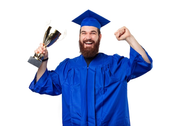 Verbaasde student man in blauw gewaad vieren en kampioen beker te houden