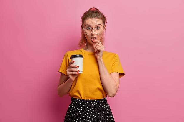 Verbaasde studente grijpt koffie tijdens de pauze, heeft een verbaasde uitdrukking, staart met ongeloof, gaat uit in de vrije tijd, draagt een transparante bril, modieuze kleding