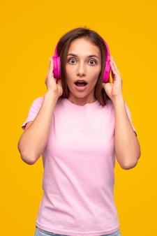 Verbaasde tienervrouw in hoofdtelefoons
