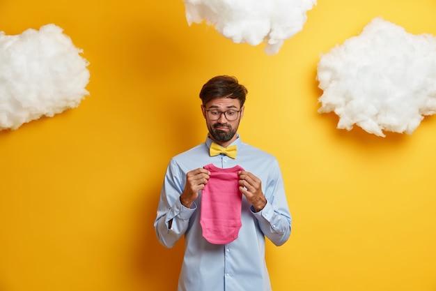 Verbaasde toekomstige vader die niet klaar is voor het vaderschap, houdt kleren voor baby, heeft geen ervaring met het zorgen voor pasgeborenen, gekleed in shirt met vlinderdas, poseert tegen gele, witte wolken