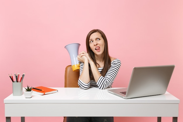 Verbaasde twijfelende vrouw die opkijkt met een tong die een megafoon vasthoudt, zit aan het witte bureau op kantoor met een pc-laptop