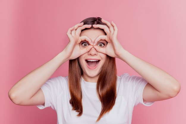 Verbaasde verbaasde funky vrouwenhanden tonen verrekijkers over roze achtergrond