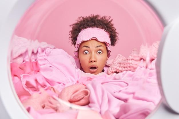 Verbaasde verbaasde huisvrouw steekt hoofd door wasgoed in wasmachine staart afgeluisterde ogen reageert op schokkend nieuws heeft veel huishoudelijk werk in handen van binnenkant wasmachine