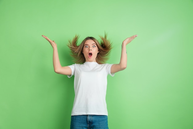 Verbaasde, verbaasde jonge vrouw die op groene studiomuur wordt geïsoleerd