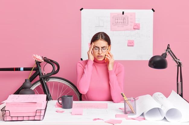 Verbaasde vermoeide vrouwelijke architect probeert de werktaak te voltooien en ontwikkelt een planningsproject dat zich concentreert op papieren poses op het bureaublad. ontevreden overwerkte vrouw grafisch ontwerper praat via mobiele telefoon