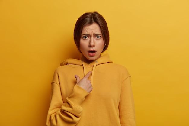 Verbaasde verontwaardigde jonge vrouw wijst naar zichzelf, verdedigt zich verbaal en kijkt met verlegenheid en ongeloof, geschokt om beschuldigd te worden, gekleed in vrijetijdskleding, poseert tegen gele muur