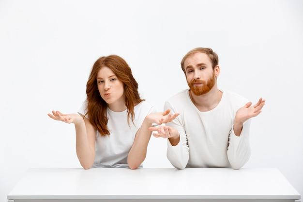 Verbaasde, verwarde roodharige man en vrouw halen hun schouders op