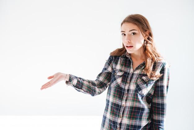 Verbaasde verwarde vrouw in de plaid shirt bedrijf copyspace op palm