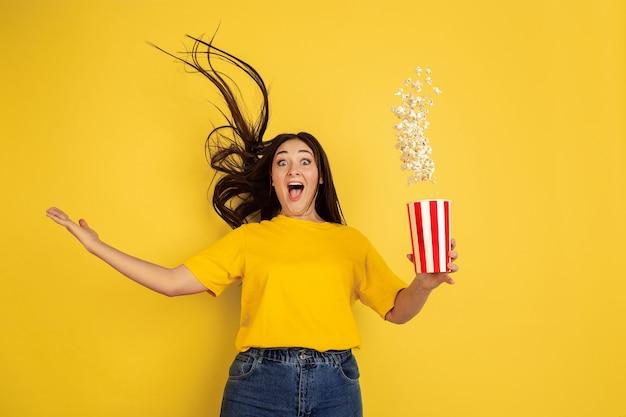 Verbaasde, vliegende popcorn. blanke vrouw portret geïsoleerd op gele muur. mooi donkerbruin model in casual. concept van menselijke emoties, gezichtsuitdrukking, verkoop, advertentie, copyspace.
