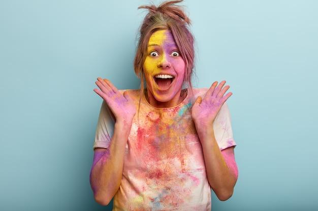 Verbaasde vrolijke vrouw brengt geweldig kleurenfestival door, lacht en spreidt haar handen zijwaarts, vuil met kleurrijk poeder, reageert vrolijk