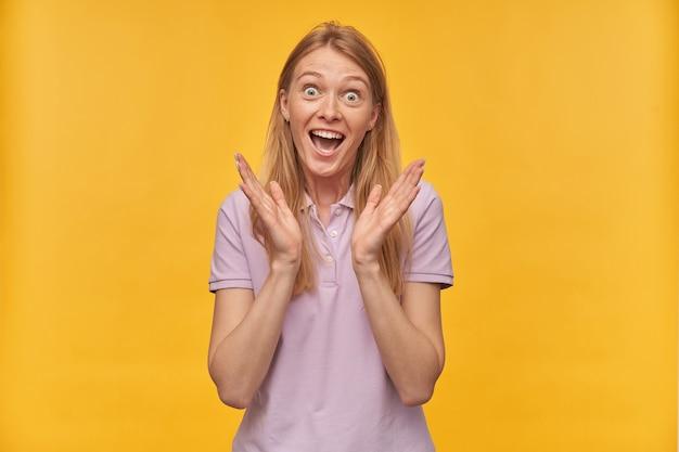 Verbaasde vrolijke vrouw met sproeten in lavendelkleurige t-shirt kepps handen omhoog en voelt zich opgewonden op geel