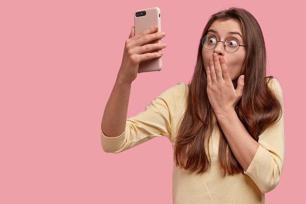 Verbaasde vrouw bedekt mond met handpalm, strares met afgeluisterde ogen, maakt videogesprek via mobiele telefoon, merkt iets schokkend op