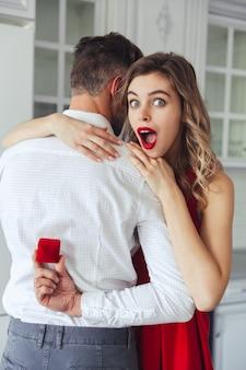 Verbaasde vrouw die doos met verlovingsring in haar echtgenoothanden bekijkt