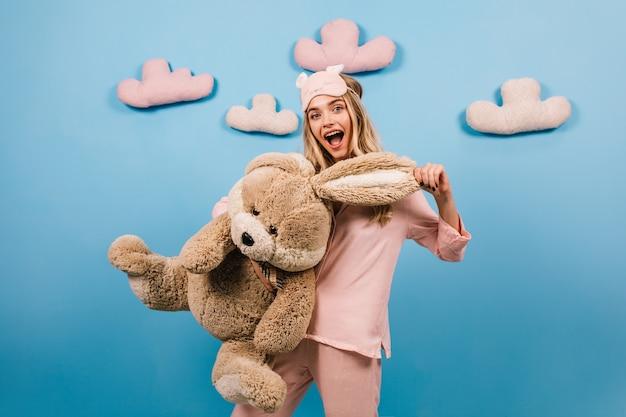 Verbaasde vrouw die groot stuk speelgoed konijn houdt