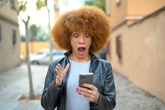 Verbaasde vrouw die het nieuws online leest in een telefoon op straat in de winter