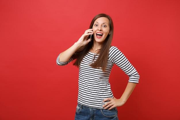 Verbaasde vrouw die mond wijd open houdt, verbaasd kijkt, praat op mobiele telefoon, aangenaam gesprek voert geïsoleerd op rode achtergrond. mensen oprechte emoties, levensstijl. bespotten kopie ruimte.