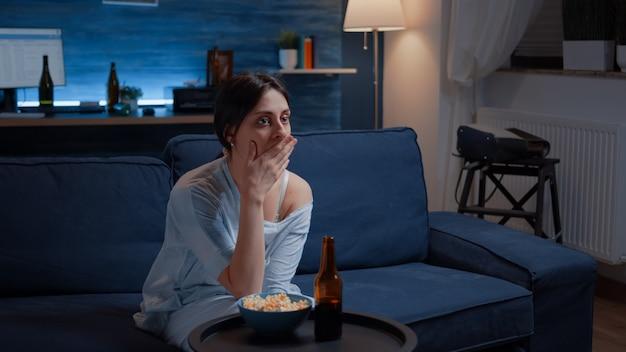 Verbaasde vrouw die naar film kijkt op tv die gezichtsuitdrukking heeft verrast