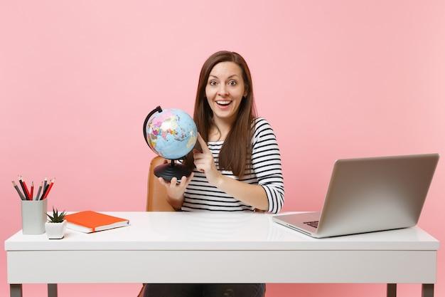 Verbaasde vrouw die wereldbol vasthoudt en vakantie plant terwijl ze zit en werkt aan een wit bureau met een moderne pc-laptop